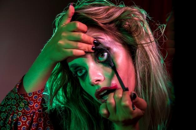 Frau gekleidet als spassvogel, der make-up verwendet