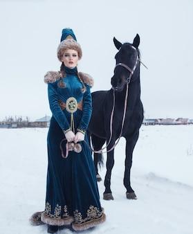 Frau gekleidet im schönen kleid in der winterlandschaft mit pferd