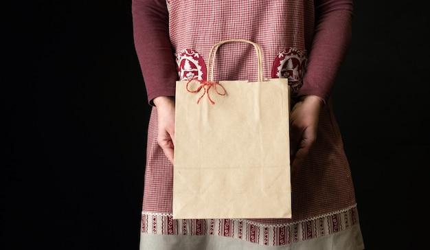Frau gekleidet in der roten festlichen schürze, die einkaufstasche am vorabend des neuen jahres hält.