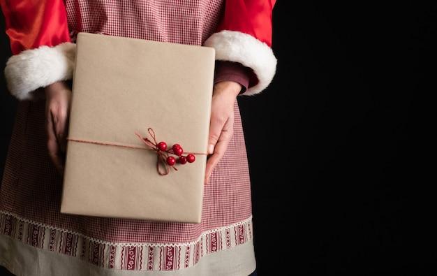 Frau gekleidet in der roten festlichen schürze, die geschenkbox am vorabend des neuen jahres hält.