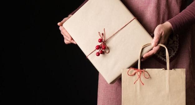 Frau gekleidet in der roten festlichen schürze, die geschenkbox und einkaufstasche am vorabend des neuen jahres hält.