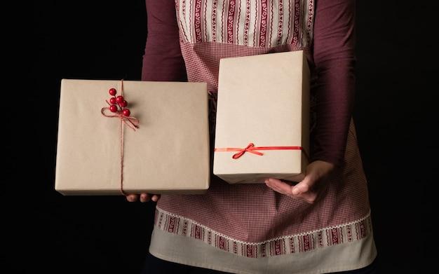 Frau gekleidet in der roten festlichen schürze, die geschenkboxen am vorabend des neuen jahres hält.