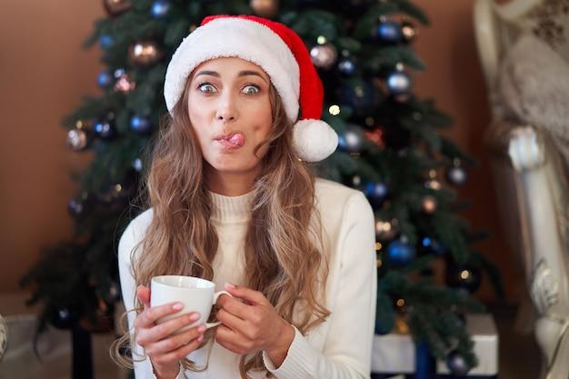 Frau gekleidete weiße pullover santa mütze und jeans sitzen auf dem boden nahe weihnachtsbaum mit geschenkbox