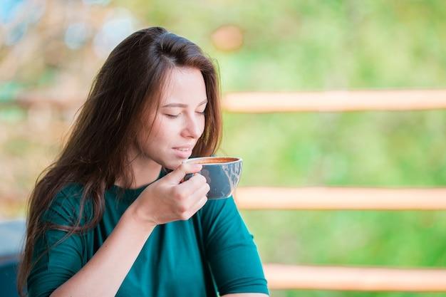 Frau genießen den geschmackvollen kaffee, der café am im freien frühstückt. trinkender kaffee der glücklichen jungen städtischen frau