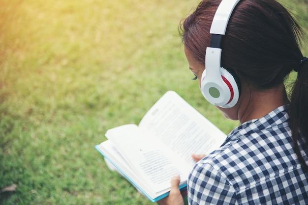 Frau genießen musik online zu hören und buch unter dem baum im öffentlichen park zu lesen. entspannungs- und bildungskonzept