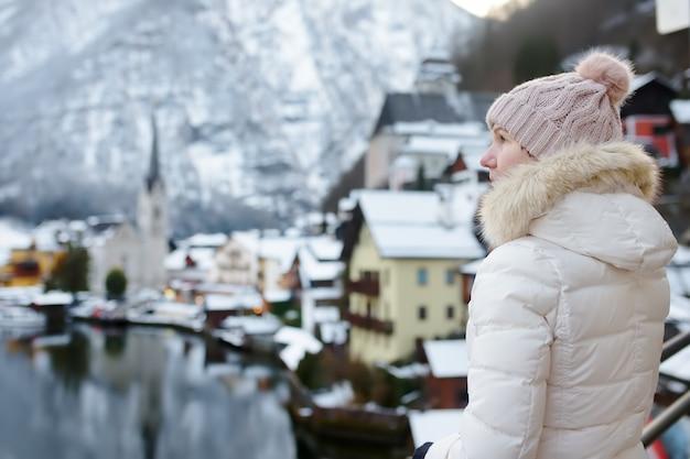 Frau genießen winteransicht des dorfes hallstatt in den österreichischen alpen
