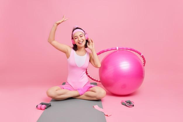 Frau genießt angenehme musik sitzt mit gekreuzten beinen auf fitnessmatte fühlt sich entspannt in activewear gekleidet hält den arm hebt das lächeln breit hat training drinnen zu hause mag sport