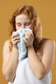 Frau genießt den geruch eines handtuchs