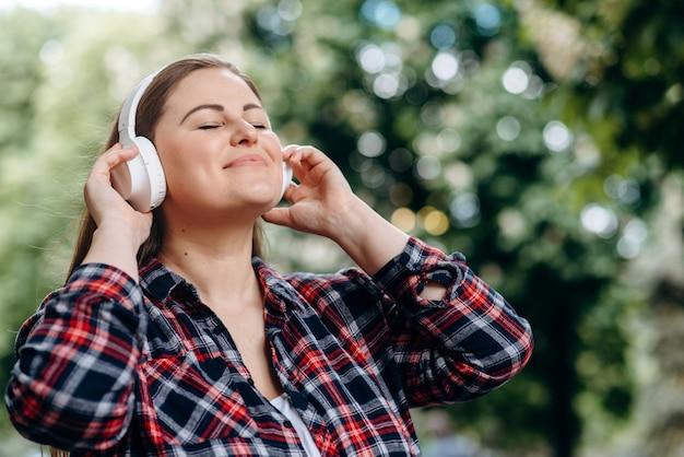Frau genießt die musik aus den kopfhörern.