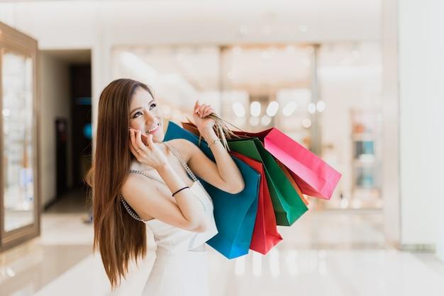 Frau genießt einkaufen und smartphone verwenden