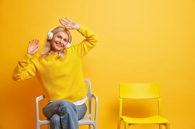 Frau genießt freizeit hebt ams hört musik über kopfhörer trägt pullover und jeans posiert auf bequemem stuhl