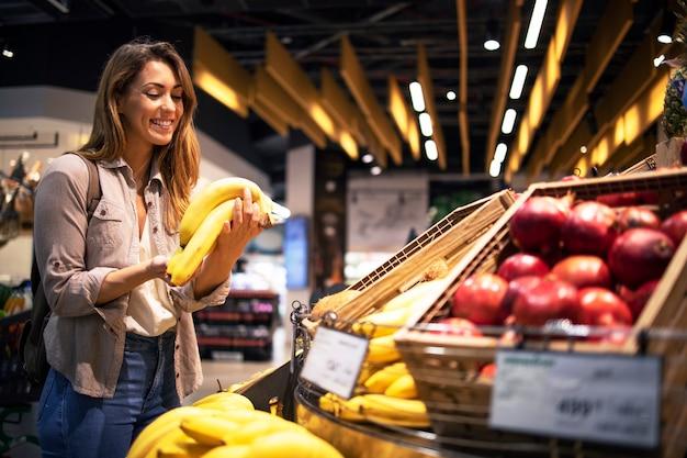 Frau genießt, gesundes essen im supermarkt zu kaufen