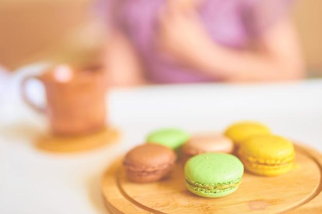 Frau genießt ihr morgenfrühstück des schwarzen kaffees, französische macarons