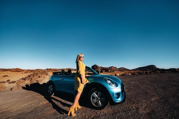 Frau genießt roadtrip, stehend mit karte in der nähe von cabrio-auto am straßenrand im vulkanischen bergwald auf der insel teneriffa, spanien.