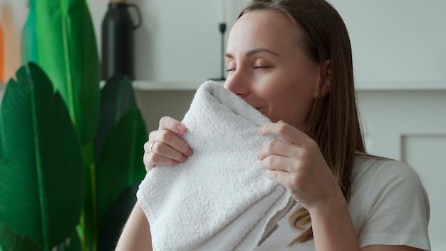 Frau genießt saubere und riechende handtücher nach dem waschen zu hause