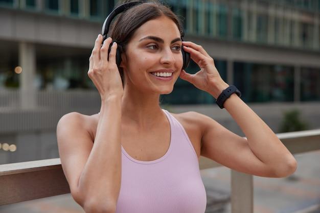 Frau genießt sportouts auf drahtlosen kopfhörern, um während des trainings musik zu hören, trägt t-shirt-posen im freien auf verschwommen