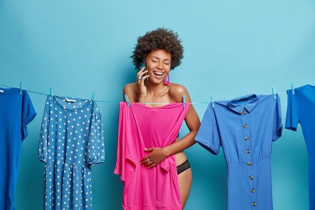 Frau genießt telefonanruf arrangiert treffen mit freund steht halbnackt hinter modischem kleid wählt modisches outfit, das isoliert auf blau getragen wird
