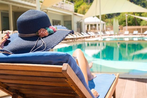 Frau genießt und entspannt auf liegestuhl am pool