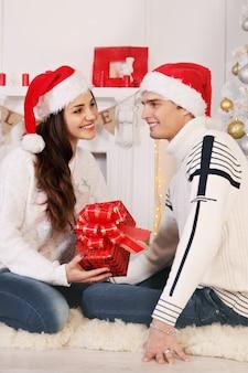 Frau gibt dem mann zu weihnachten ein geschenk