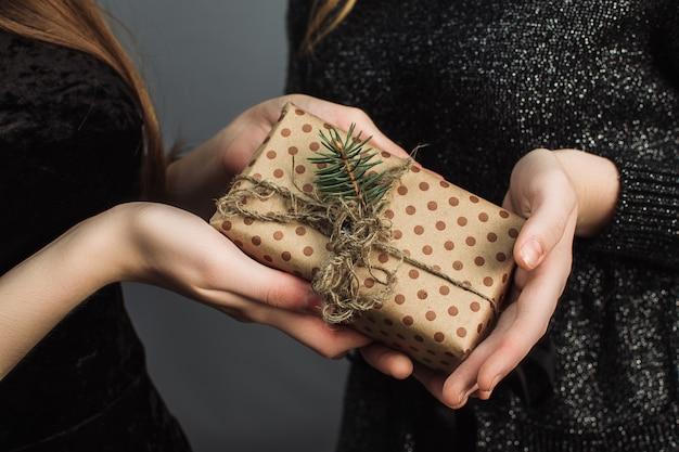 Frau gibt einem freund ein weihnachtsgeschenk, das mit ihren eigenen händen gemacht wird