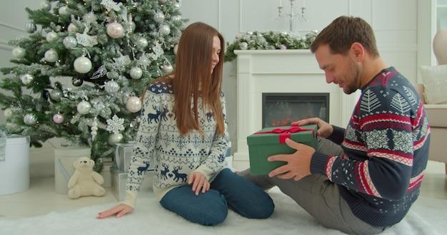Frau gibt einem mann weihnachtsgeschenk. neujahrsatmosphäre zu hause