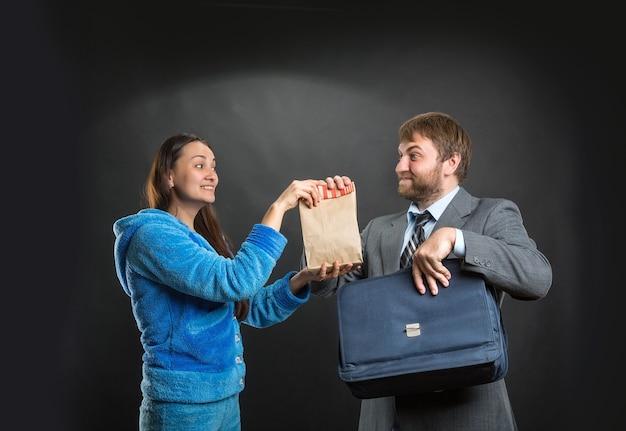 Frau gibt ihrem mann eine packung mit snack