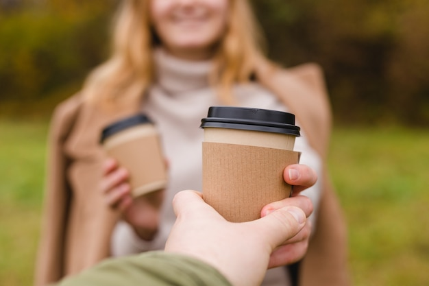 Frau gibt papierkaffeetasse mann nimmt eine tasse