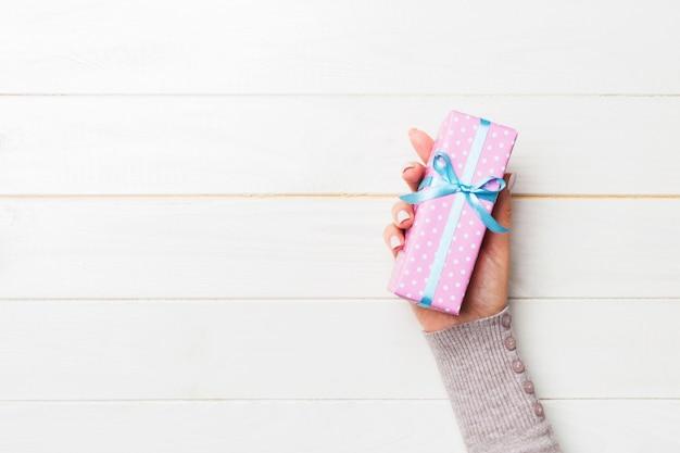 Frau gibt valentinsgrußgeschenkbox mit blauem bogen