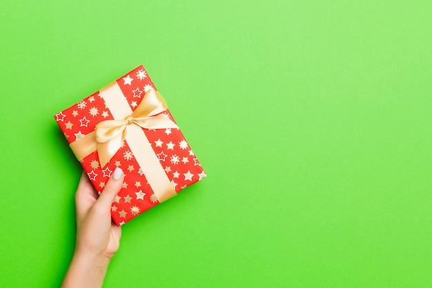 Frau gibt valentinsgrußgeschenkbox mit goldenem bogen