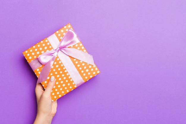 Frau gibt valentinsgrußgeschenkbox mit rosa bogen