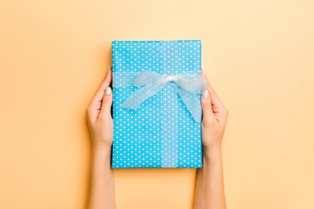 Frau gibt valentinsgrußgeschenkbox mit weißem bogen