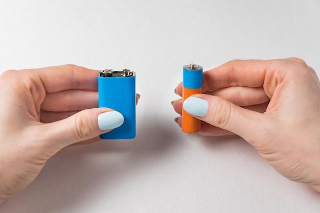 Frau gibt zwei batterien auf einer weißen oberfläche. generische aa und pp3 batterie und akku