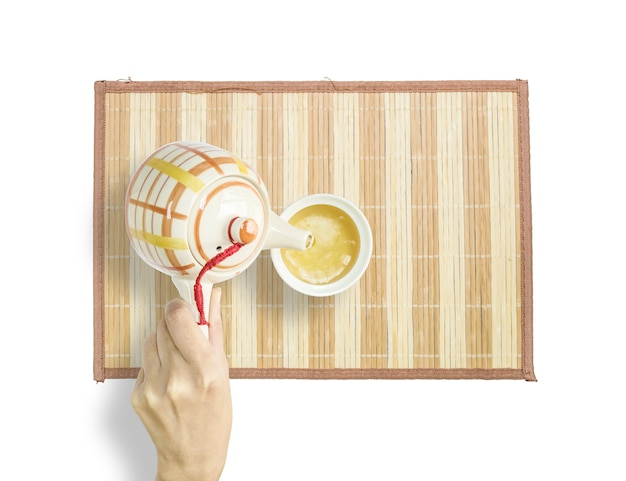 Frau gießen heißen tee von einer teekanne zu einer schale auf der hölzernen matte, die auf weißem hintergrund lokalisiert wird