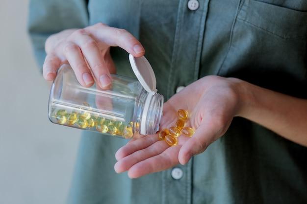 Frau gießt aus einem glas pillen mit lebertran. seitenansicht