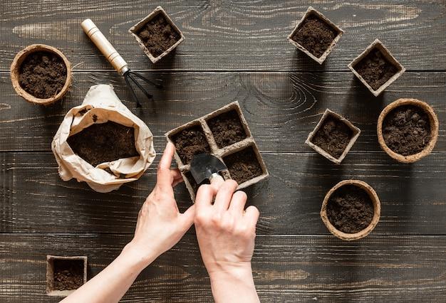 Frau gießt boden in die umweltfreundlichen töpfe, um setzlinge, töpfe an der holzwand, kleine tasche mit boden- und gartenkelle und rechen zu pflanzen