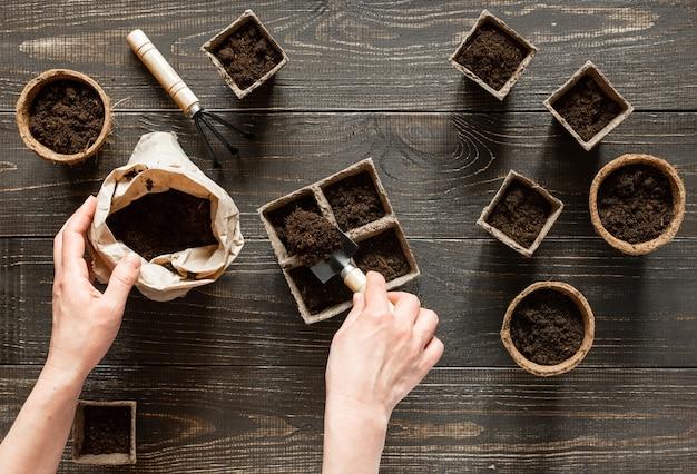 Frau gießt boden in die umweltfreundlichen töpfe, um setzlinge zu pflanzen