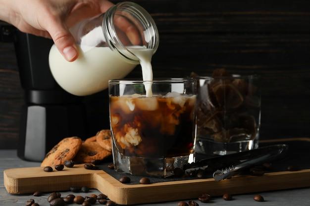 Frau gießt eine milch in ein glas kaffee. zusammensetzung mit eiskaffee