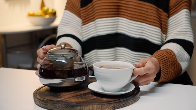 Frau gießt eine tasse tee aus dem wasserkocher auf der küchentheke