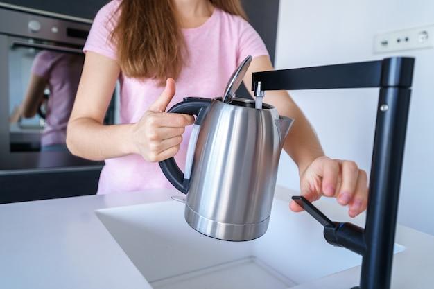 Frau gießt frisches sauberes gefiltertes gereinigtes wasser aus einem wasserhahn in einen wasserkocher zum kochen von wasser in der küche zu hause