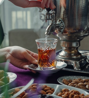 Frau gießt heißes wasser in glas mit schwarzem tee aus samowar