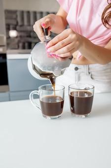Frau gießt kaffee in gläser auf küchenhintergrund