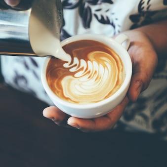 Frau gießt kaffeesahne