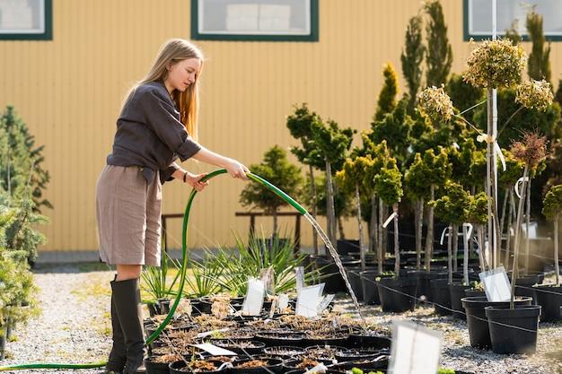 Frau gießt pflanzen mit schläuchen