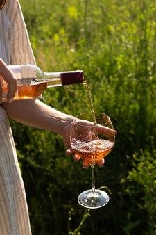 Frau gießt roséwein in ein glas in einem sommergarten