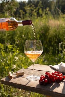 Frau gießt roséwein in ein glas