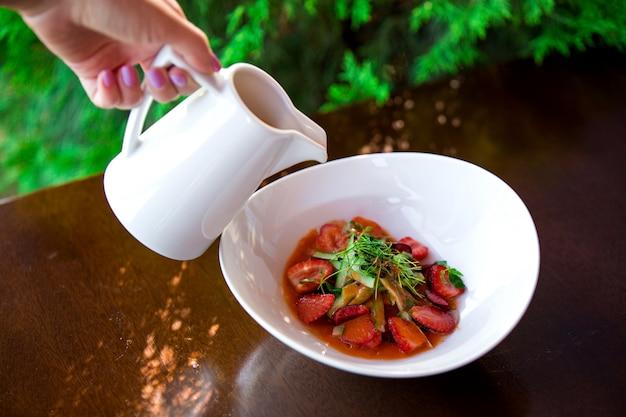 Frau gießt soße in erdbeer- und gurkensalat