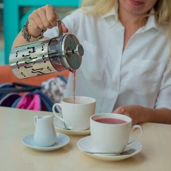 Frau gießt tee in eine tasse nahaufnahme