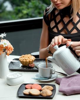 Frau gießt tee in eine tasse