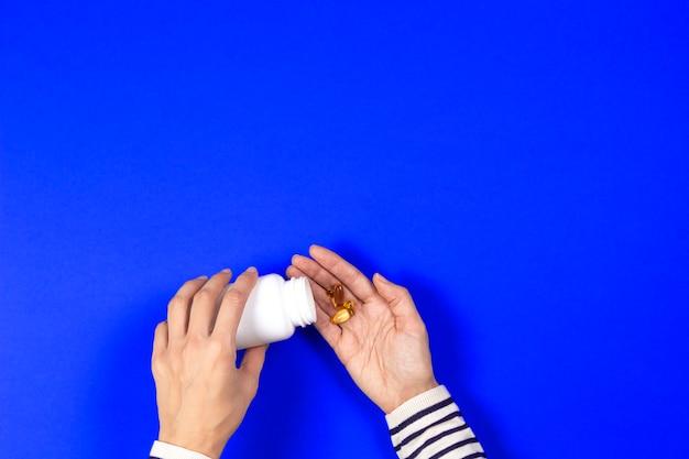 Frau gießt von weißen flasche gelben kapseln von omega 3 auf blauem hintergrund