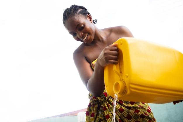 Frau gießt wasser aus einem gelben behälter